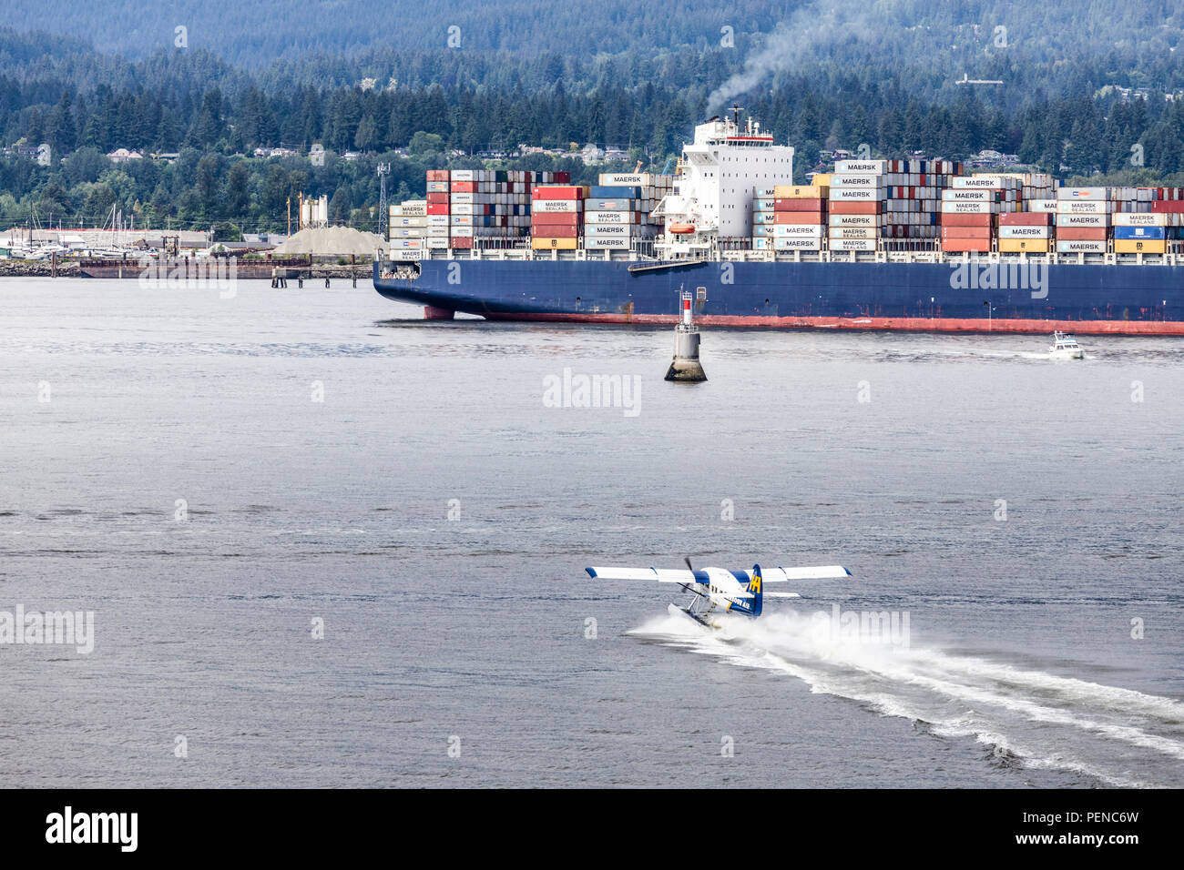 A tourist seaplane taking off in quite close proximity to the container ship Seamax Stratford in the harbour at Vancouver, British Columbia, Canada - Stock Image