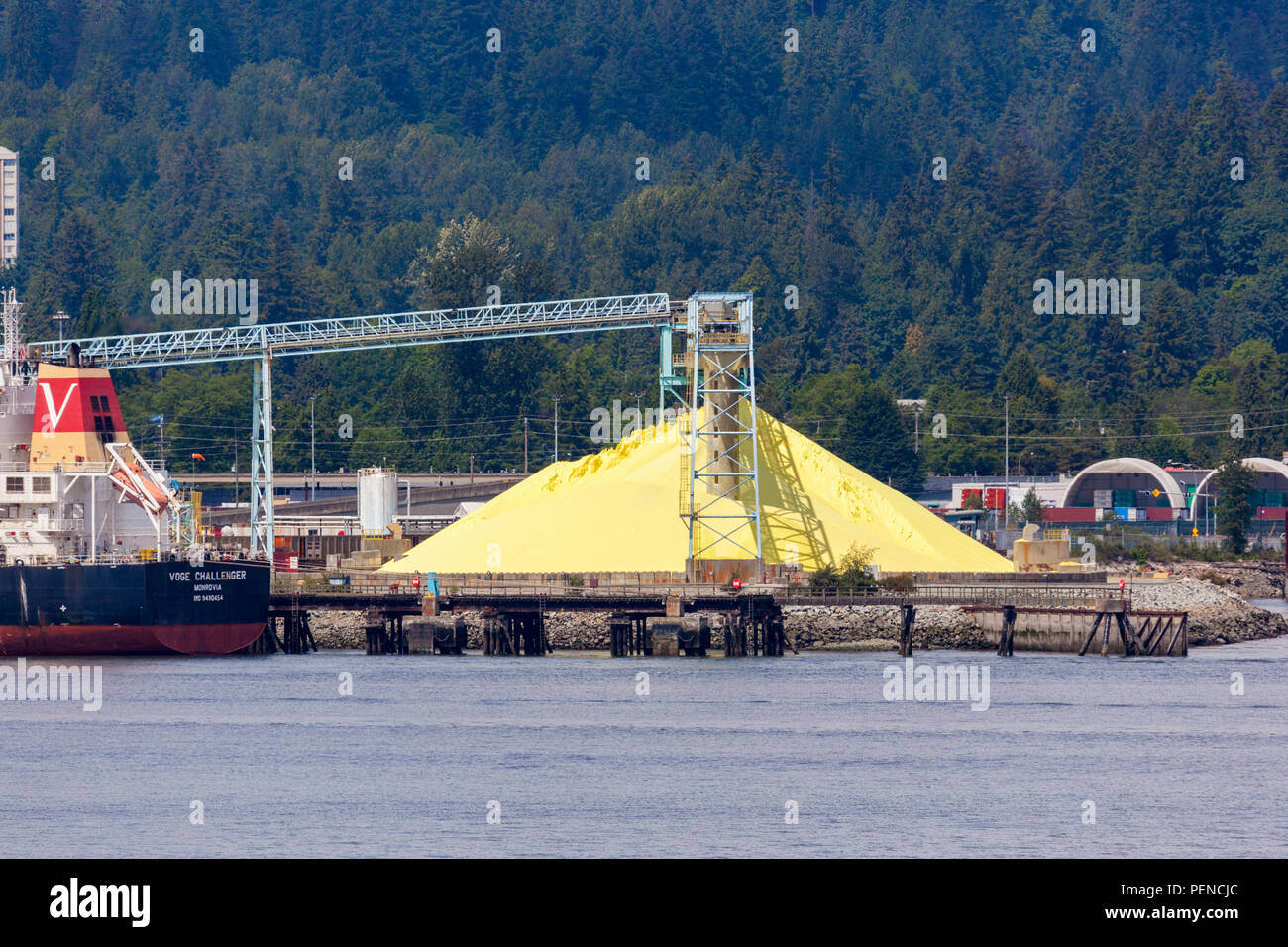 A heap of sulphur awaiting export by the bulk carrier Voge Challenger from the harbour at North Vancouver, British Columbia, Canada - Stock Image