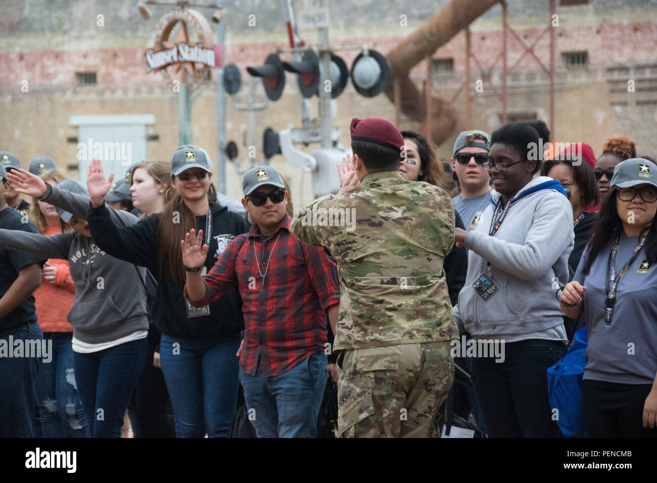Army All-American Bowl Soldier Mentor, Staff Sgt. Ryann Sartor, with USASOC's 95th Civil Affairs, runs through a crowd of high students visiting the Army Experience Zone at Sunset Station in San Antonio. The Army All-American Bowl airs live on NBC at 1 p.m., EST. - Stock Image