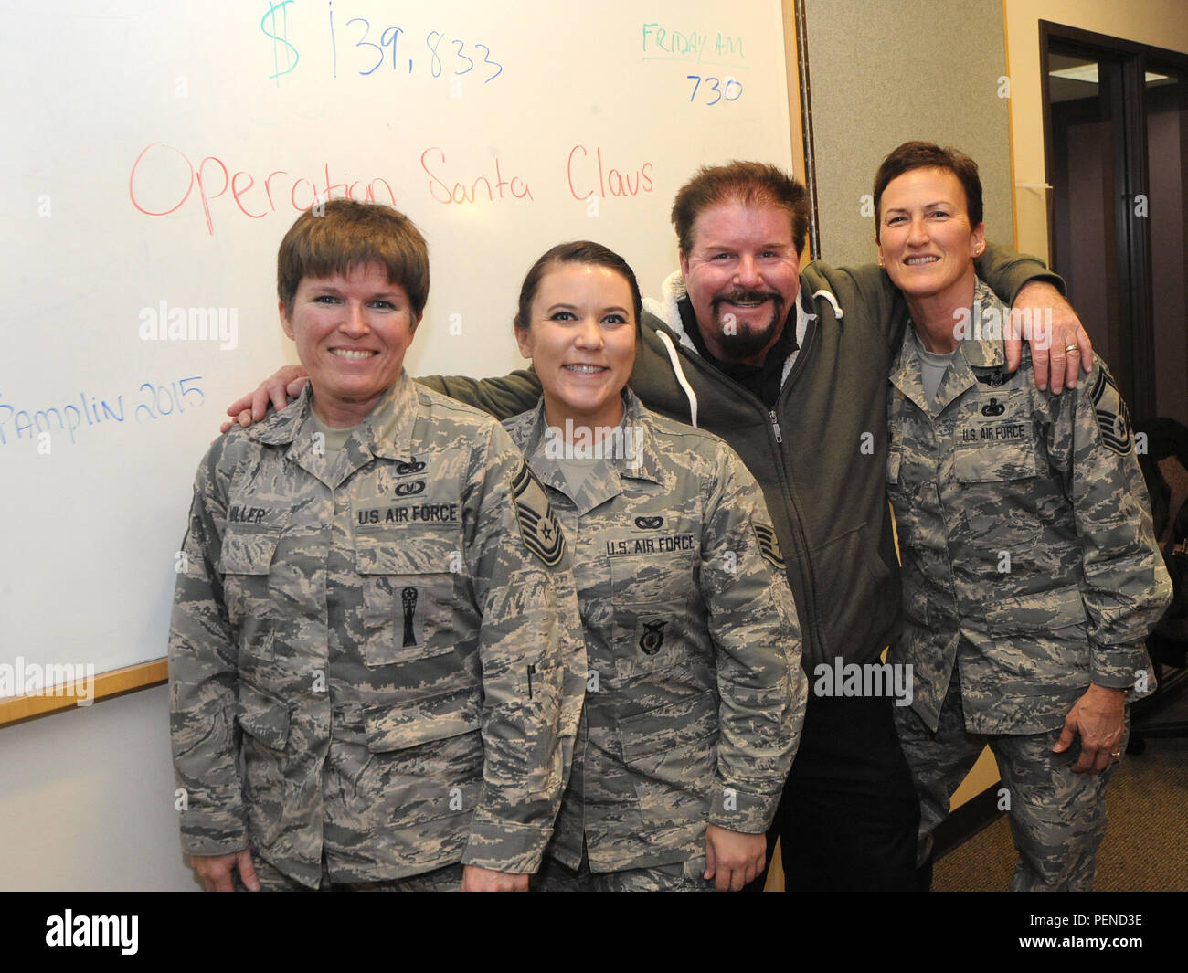 Terry Boyd, KPAM Radio 860 host, pauses for a photograph with Senior Master Sgt. Kristen Miller, left, Staff Sgt. Sara Wassam, center, and Senior Master Sgt. Pam Pittman, right, during Operation Santa Claus, an annual fundraiser, which assists local families coping with income loss due to military deployment, Dec. 4, 2015, in Clackamas, Ore. (U.S. Air Force photo by Tech. Sgt. John Hughel, 142nd Fighter Wing Public Affairs) - Stock Image