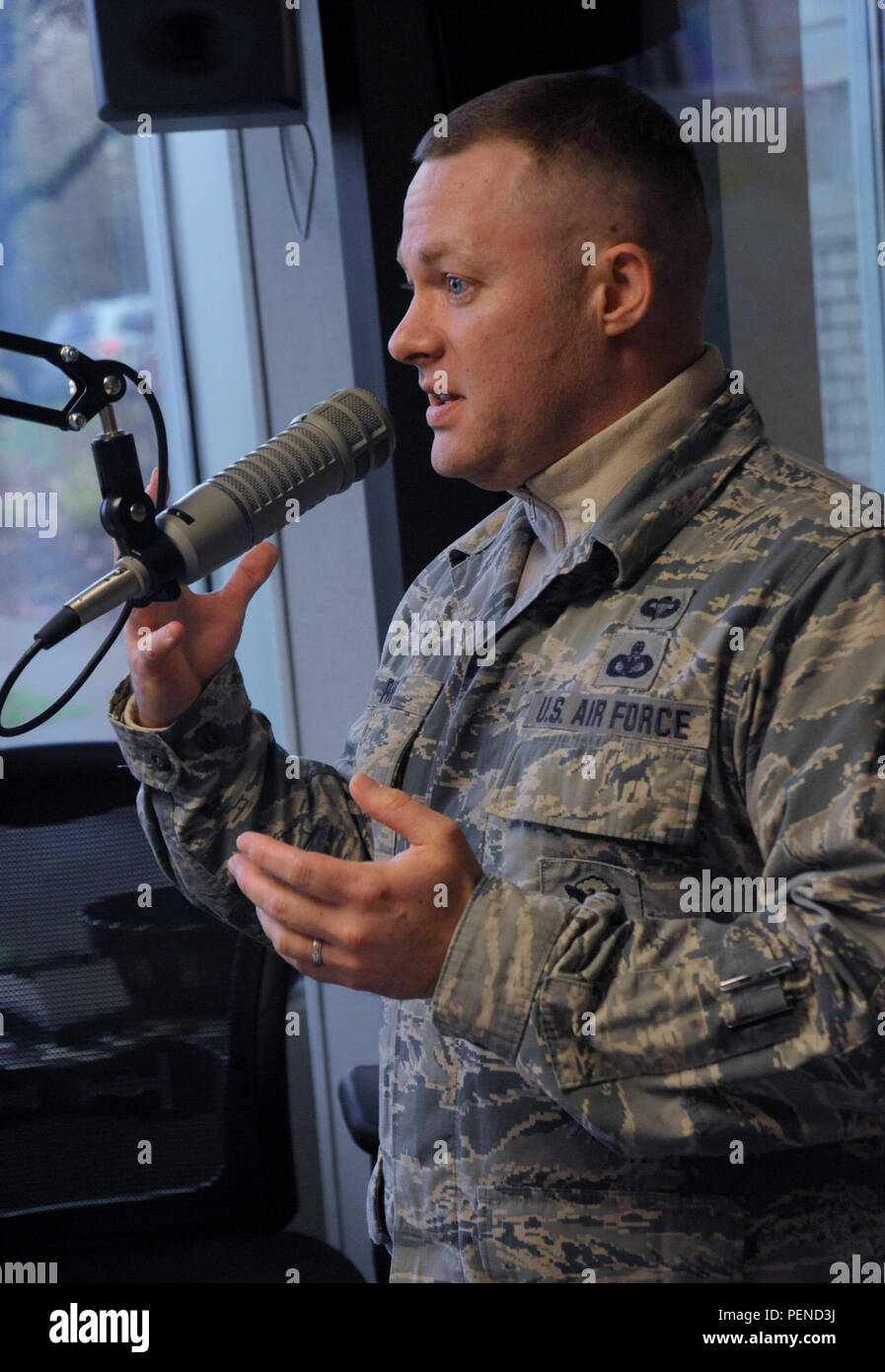 Oregon Master Sgt. Christopher Rich, assigned to the 142nd Fighter Wing Security Forces Squadron, talks on air with KPAM 860 host Bob Miller during his program, in Clackamas, Ore., Dec. 4, 2015, as part of Operation Santa Claus, an annual fundraiser, which assists local families coping with income loss due to military deployment. (U.S. Air Force photo by Tech. Sgt. John Hughel, 142nd Fighter Wing Public Affairs) - Stock Image