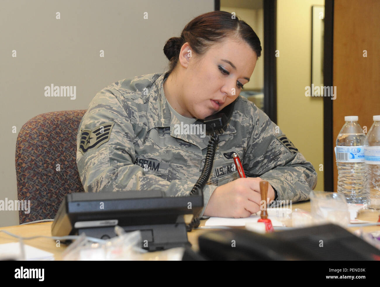 Oregon Staff Sgt. Sara Wassam, assigned to the 142nd Fighter Wing Security Forces Squadron, answers phone calls at KPAM 860 radio, in Clackamas, Ore., Dec. 4, 2015, helping raise money for Operation Santa Claus, an annual fundraiser, which assists local families coping with income loss due to military deployment. (U.S. Air Force photo by Tech. Sgt. John Hughel, 142nd Fighter Wing Public Affairs) - Stock Image