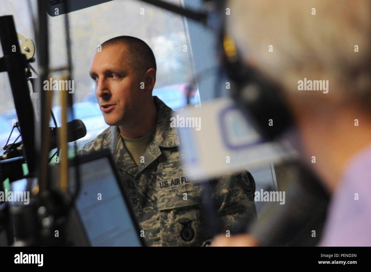 Oregon Air National Guard Master Sgt. Matt Kochosky talks on air during the Mark and Dave Radio Program, KPAM 860 radio, as part of Operation Santa Claus, an annual fundraiser, which assists local families coping with income loss due to military deployment, Dec. 4, 2015, in Clackamas, Ore. (U.S. Air Force photo by Tech. Sgt. John Hughel, 142nd Fighter Wing Public Affairs) - Stock Image