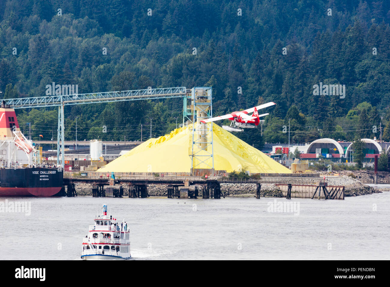A tourist seaplane taking off in quite close proximity to the pile of sulphur in the harbour at North Vancouver, British Columbia, Canada - Stock Image