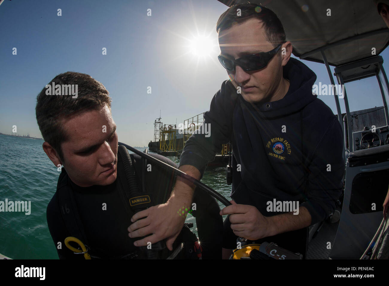 160106-N-BJ294-026 NAVAL SUPPORT ACTIVITY BAHRAIN (Jan. 6, 2016) Navy Diver 1st Class Scott Colvin conducts gear checks on Navy Diver 3rd Class Dakota Helm, assigned to Commander, Task Group (CTG) 56.1, prior to conducting an anti-terrorism force protection dive. CTG 56.1 conducts mine countermeasures, explosive ordnance disposal, salvage-diving and force protection operations throughout the U.S. 5th Fleet area of operations. (U.S. Navy Combat Camera photo by Mass Communication Specialist 2nd Class Wyatt Huggett/Released) - Stock Image