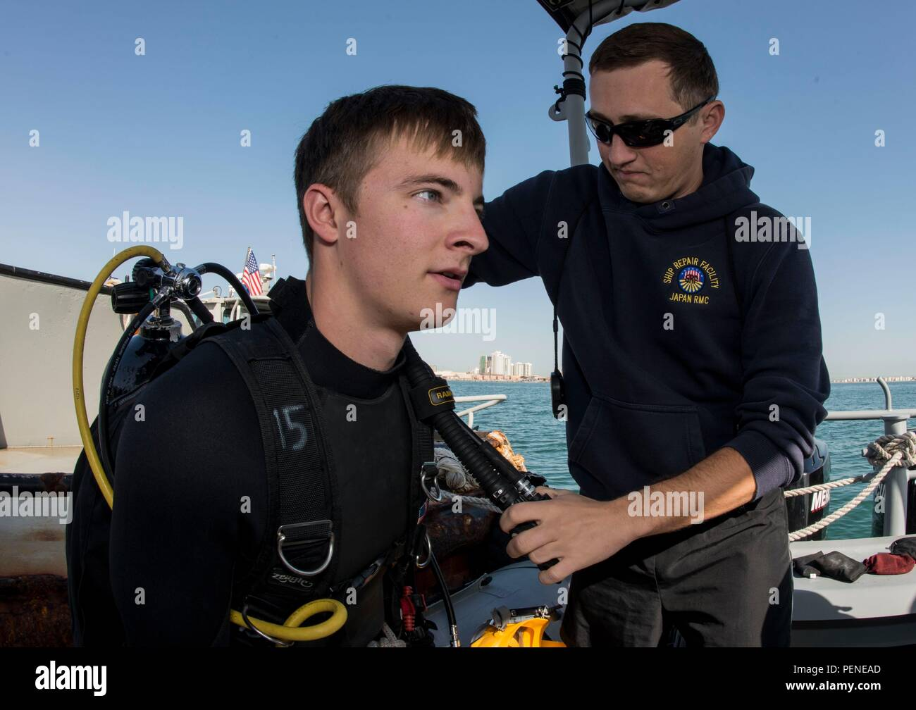 160106-N-BJ294-020 NAVAL SUPPORT ACTIVITY BAHRAIN (Jan. 06, 2016) Navy Diver 1st Class Scott Colvin conducts gear checks on Navy Diver 3rd Class Darren Hauk, assigned to Commander, Task Group (CTG) 56.1, prior to conducting an anti-terrorism force protection dive. CTG 56.1 conducts mine countermeasures, explosive ordnance disposal, salvage-diving and force protection operations throughout the U.S. 5th Fleet area of operations. (U.S. Navy Combat Camera photo by Mass Communication Specialist 2nd Class Wyatt Huggett/Released) - Stock Image