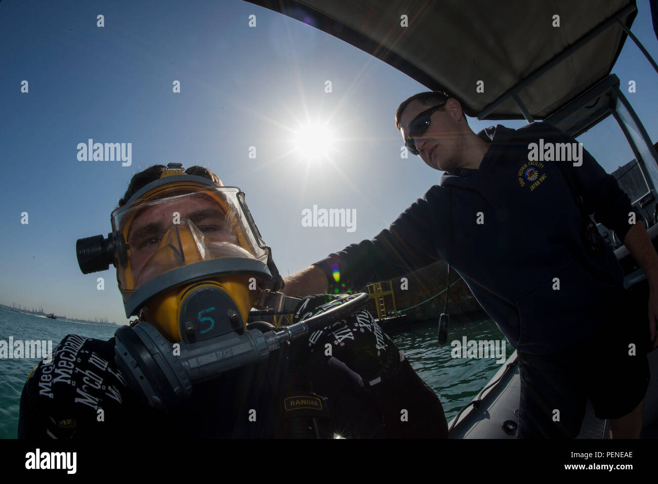 160106-N-BJ294-032 NAVAL SUPPORT ACTIVITY BAHRAIN (Jan. 6, 2016) Navy Diver 1st Class Scott Colvin conducts gear checks on Navy Diver 3rd Class Dakota Helm, assigned to Commander, Task Group (CTG) 56.1, prior to conducting an anti-terrorism force protection dive. CTG 56.1 conducts mine countermeasures, explosive ordnance disposal, salvage-diving and force protection operations throughout the U.S. 5th Fleet area of operations. (U.S. Navy Combat Camera photo by Mass Communication Specialist 2nd Class Wyatt Huggett/Released) - Stock Image