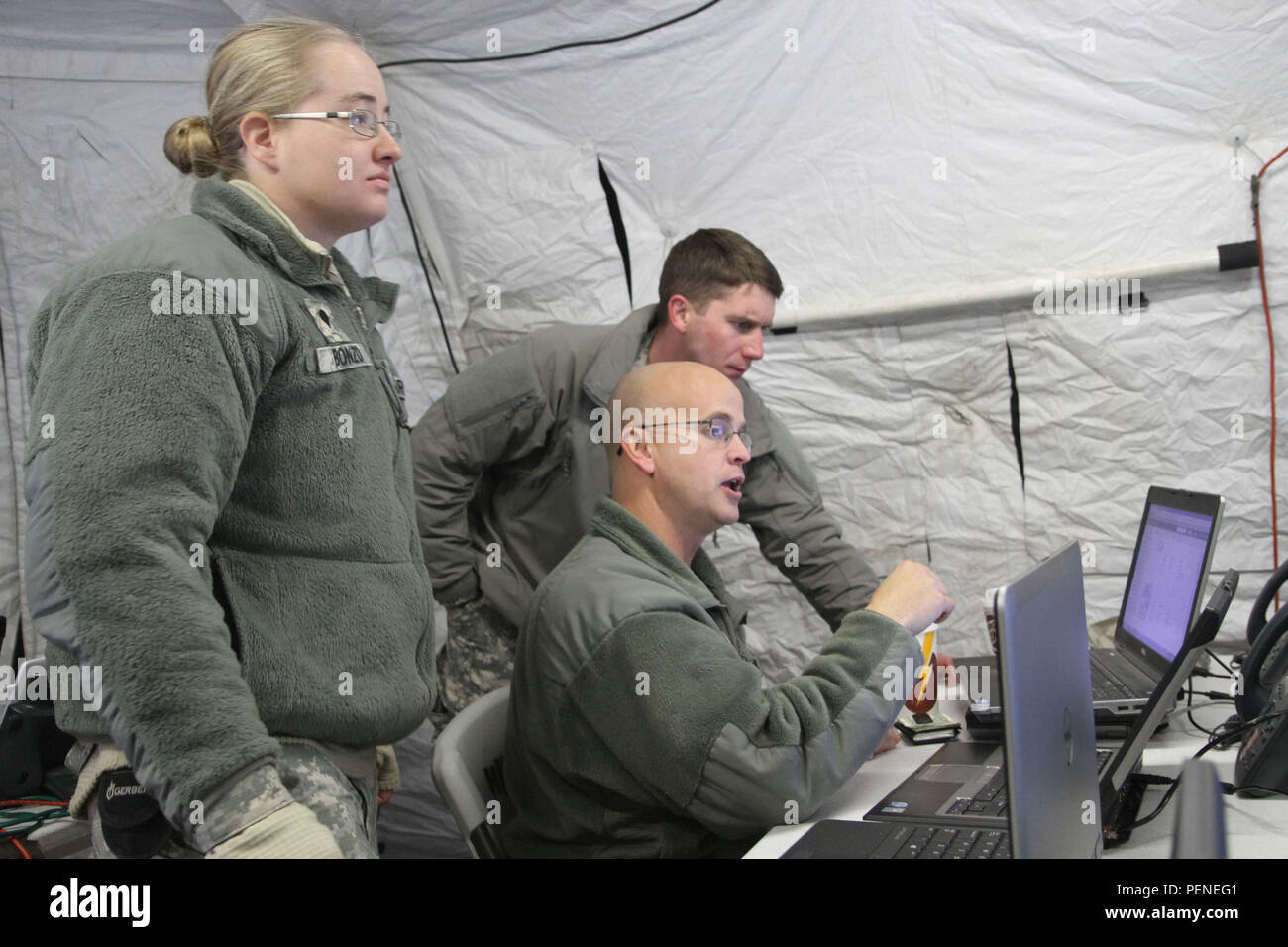 Army National Guard Spc. Tracy Bonzo, Master Sgt. Clifford Julian and Staff Sgt. Brian Carroll work to coordinate and communicate with leaders during a winter emergency response training exercise at the 168th Regiment, Regional Training Institute at Fort Carson, Colo., Jan. 9, 2016. The exercise combined Colorado National Guard forces with civilian authorities across the state to gain skills for quick and efficient emergency response. Stock Photo