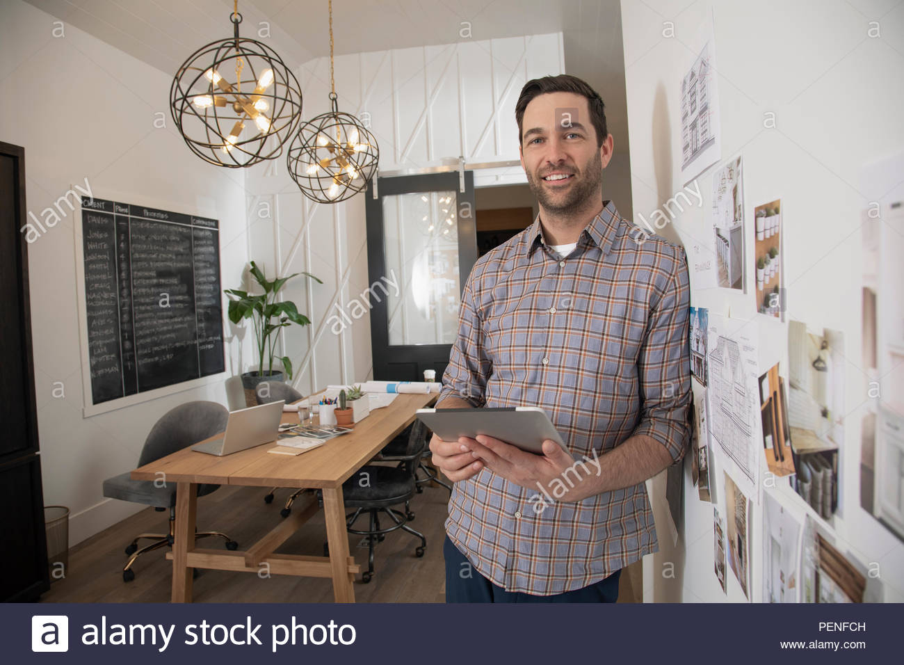 Portrait confident home builder architect with digital tablet in office - Stock Image