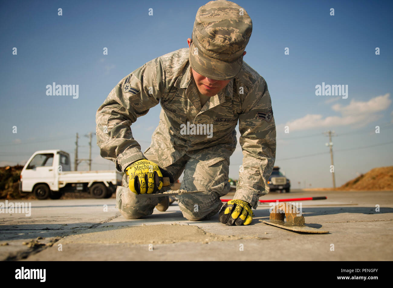 Airman 1st Class Brendan Kinser, 374th Civil Engineer Squadron pavements and equipment apprentice, performs a spall repair on a section of Yokota Air Base, Japan, Jan. 13, 2016. Aptly named 'Dirt Boys,' 374 CES pavement and equipment Airmen perform spall repairs as part of their preventative maintenance practices to ensure Yokota's airfield is free of cracks and tears. (U.S. Air Force photo by Airman 1st Class Delano Scott/Released) - Stock Image