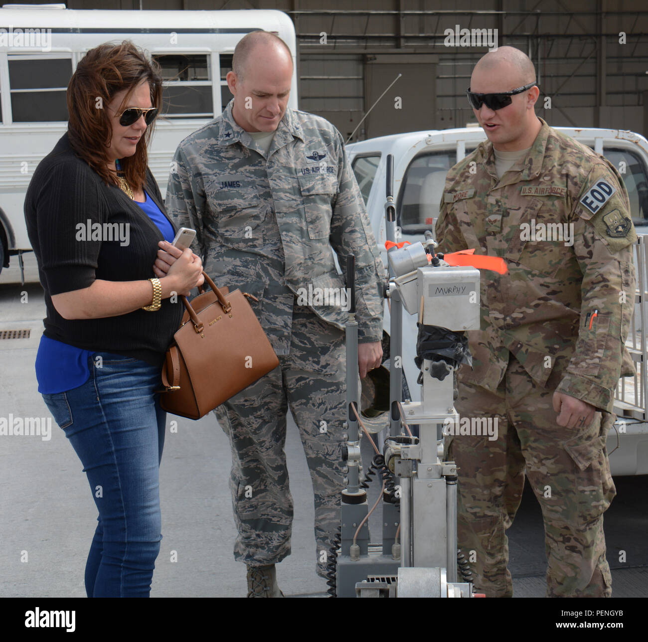 Brig. Gen. Darren James, 379th Air Expeditionary Wing commander, and his wife, Melissa James, listen to Senior Airman Taylor Moore, 379th Expeditionary Civil Engineer Squadron Explosive Ordnance Flight technician; explain how the F-6 robot operates during the annual Flight Line Fest at Al Udeid Air Base, Qatar, Jan. 10. The F-6 robot helps EOD technicians find explosives. Flight Line Fest is a joint partnership between the 379 AEW and Qatar Emiri Air Force held to foster relations between Qatar and the United States. (U.S. Air Force photo by Tech. Sgt. James Hodgman/Released) - Stock Image