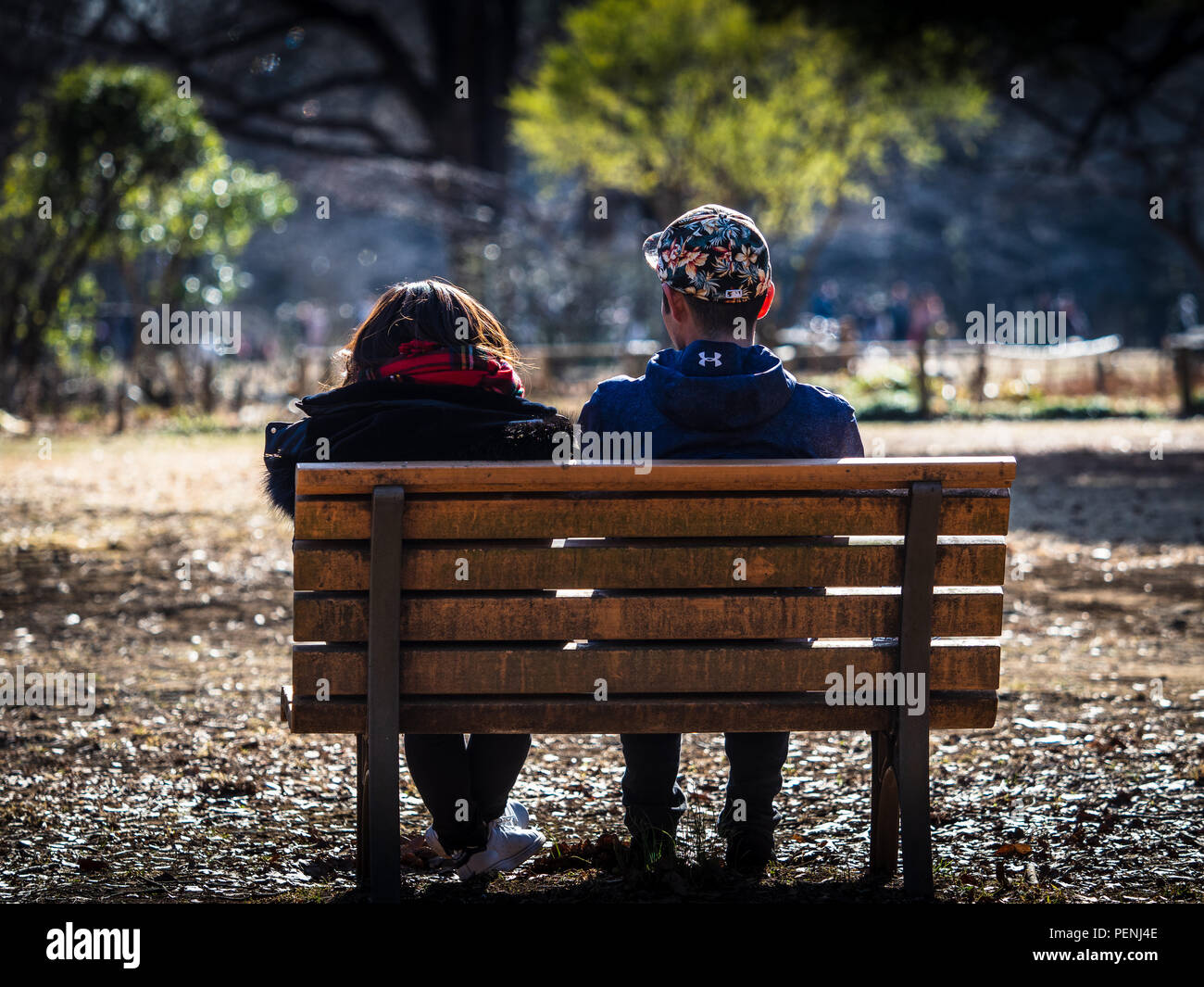 Park Life Tokyo Yoyogi Park - a couple relax on a park bench in Yoyogi Park in Shibuya-ku Tokyo Japan - Stock Image