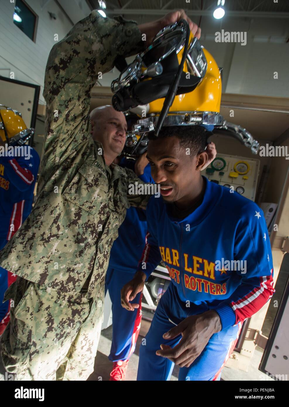 151213-N-CJ186-616 NAVAL SUPPORT ACTIVITY BAHRAIN (Dec. 13, 2015) Senior Chief Navy Diver Russell Ciardiello, assigned to Commander, Task Group 56.1, assists Harlem Globetrotter, Bull Bullard, to don a Kirby Morgan diving helmet during a command tour. The Harlem Globetrotters took an afternoon to meet service members stationed in the Kingdom of Bahrain during their 2016 World Tour, presented by Navy Entertainment and Armed Forces Entertainment. CTG 56.1 conducts mine countermeasure, explosive ordnance disposal, salvage-diving, and force protection operations throughout the 5th Fleet area of op - Stock Image
