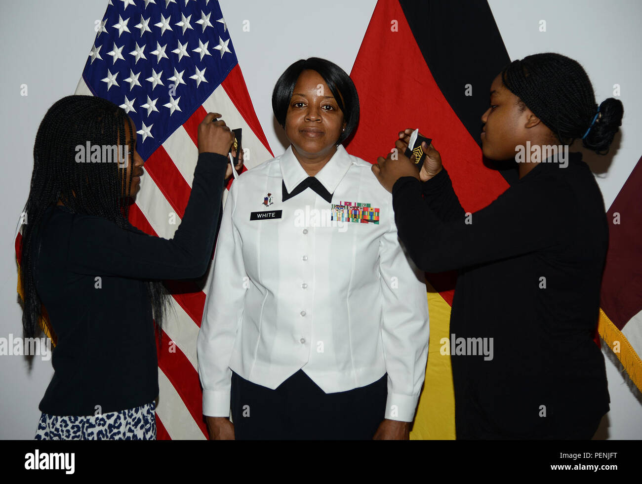 Command Sgt. Maj. Diahann J. White has her daughters put on her new rank during her lateral promotion ceremony prior to her assignment as command sergeant major of the 121st Combat Support Hospital in Yongsan, South Korea, on Dec. 16, 2015, in Sembach, Germany. Approximately 12 percent of E-9s in the U.S. Army are chosen for command sergeant major positions and in the Army Medical Department the percentage for these positions is around 11 percent (Photo by Elisabeth Paqué, 7th US Army JMTC Visual Information Specialist). Stock Photo