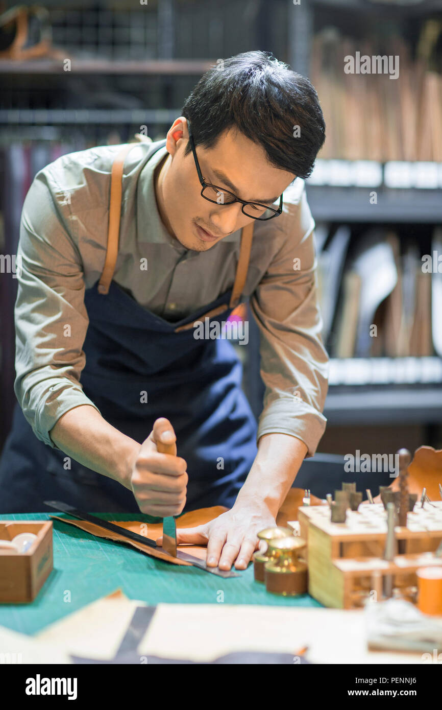 Young leather craftsman working in studio Stock Photo
