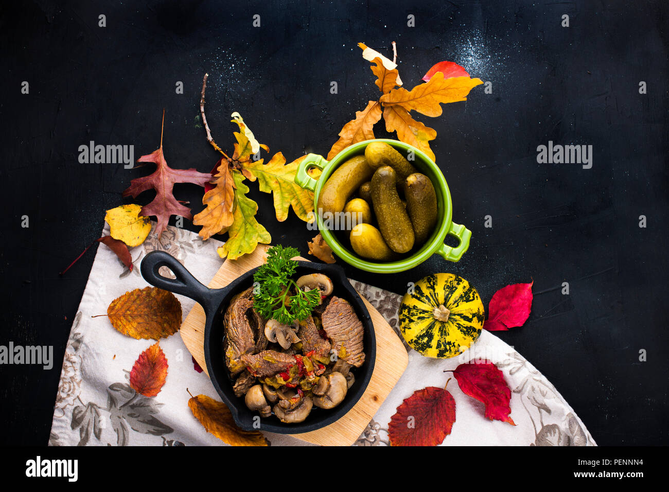 fried meat with mushrooms in a frying pan. on a black background. Lunch with autumn leaves. Top view. - Stock Image