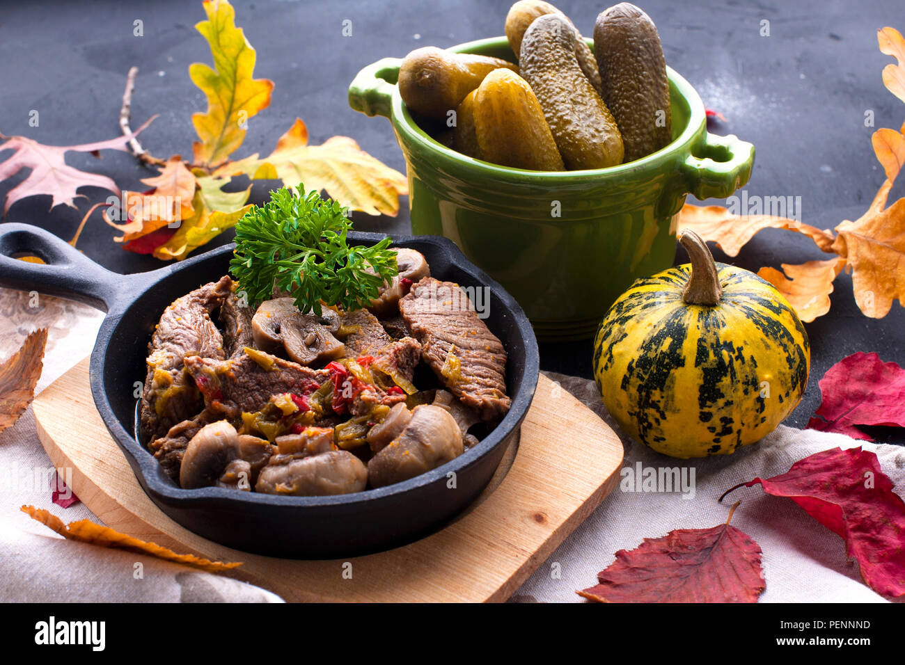 fried meat with mushrooms in a frying pan. on a black background. Lunch with autumn leaves. Top view Stock Photo
