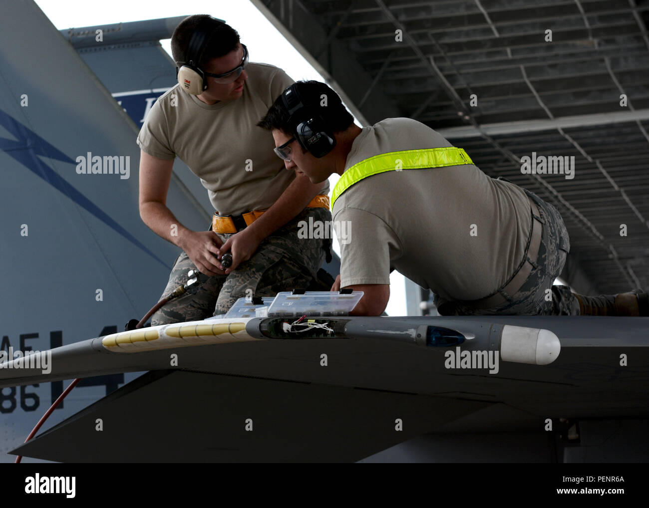 Two U.S. Air Force airmen from the 125th Fighter Wing Machine shop work on an F-15C Eagle wing to repair damaged fasteners in Jacksonville, Fla., Jan. 9, 2016. (U.S. Air National Guard photo by Tech. Sgt. Troy Anderson/Released) - Stock Image