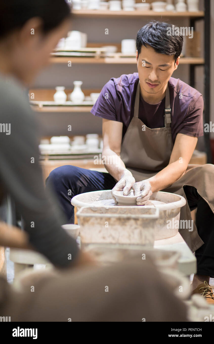 Happy young colleagues making potteries - Stock Image