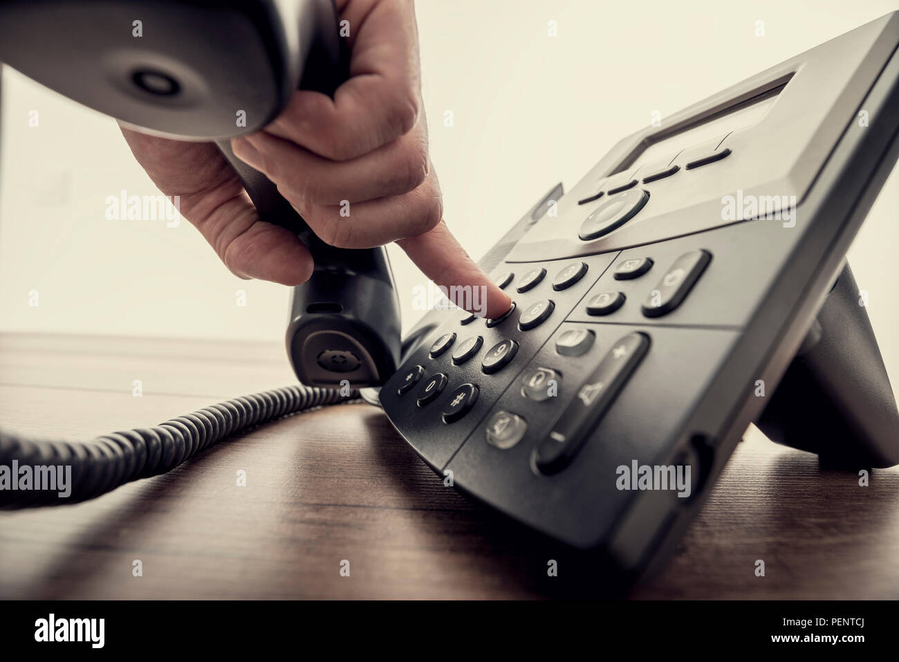 Closeup of male hand holding telephone receiver and dialing a phone number on a classical black landline telephone. Retro filter effect. - Stock Image
