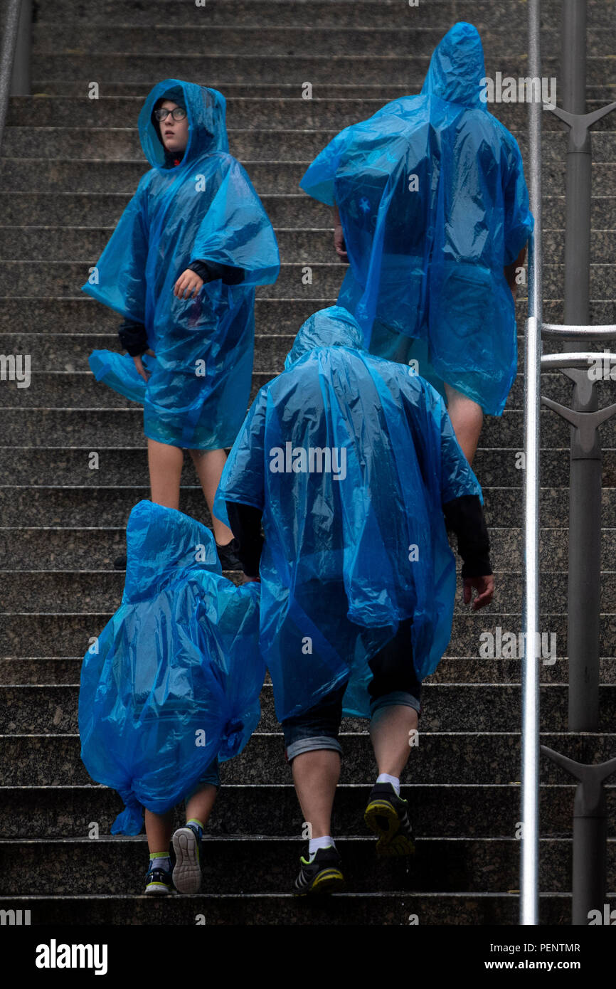 A group of people wear ponchos in the rain outside Wembley Park Station in north London. - Stock Image