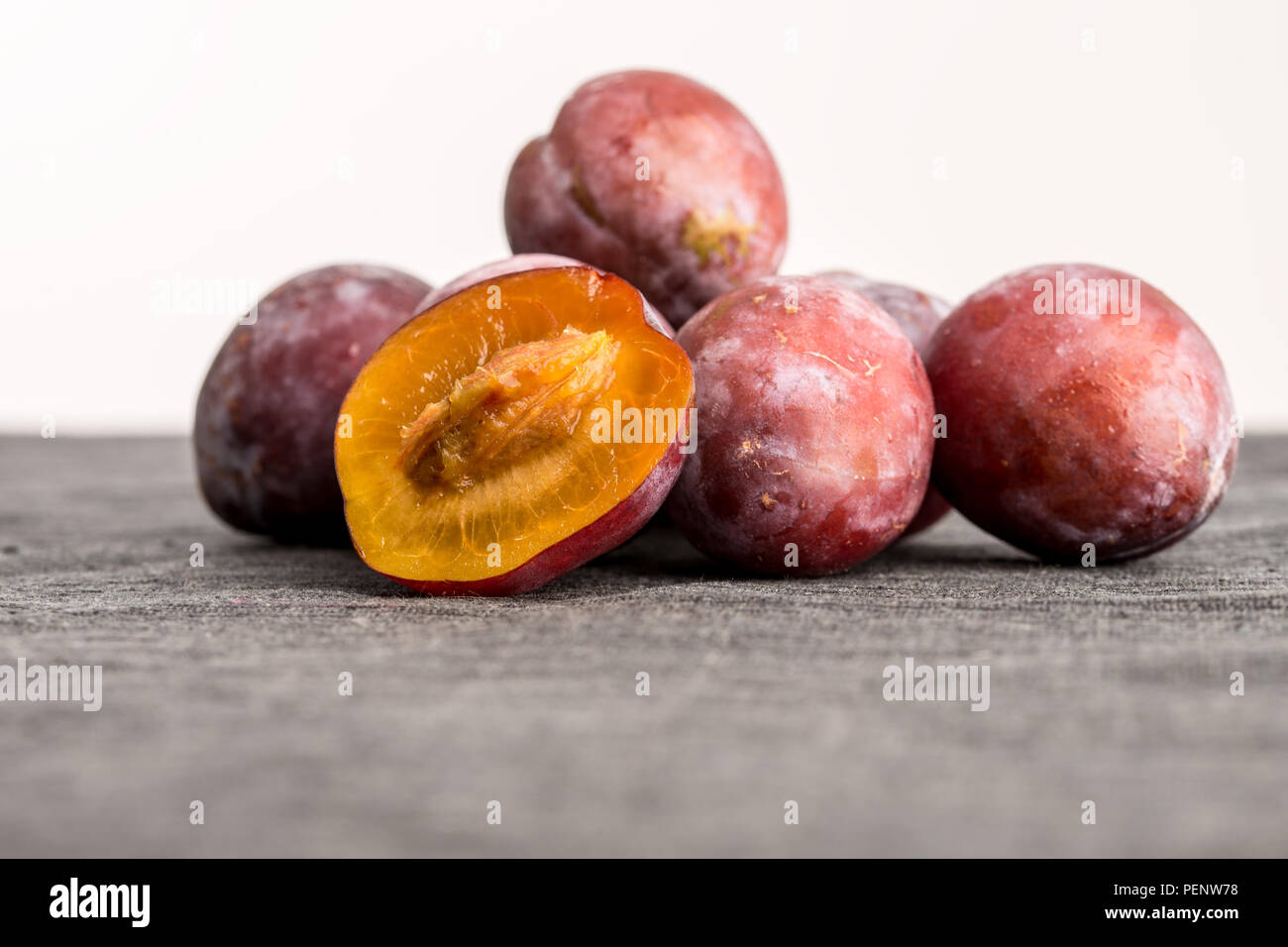 Heap of whole fresh plums with one halved one balanced in front showing the juicy texture of the orange flesh and the stone or pip, low angle with cop Stock Photo