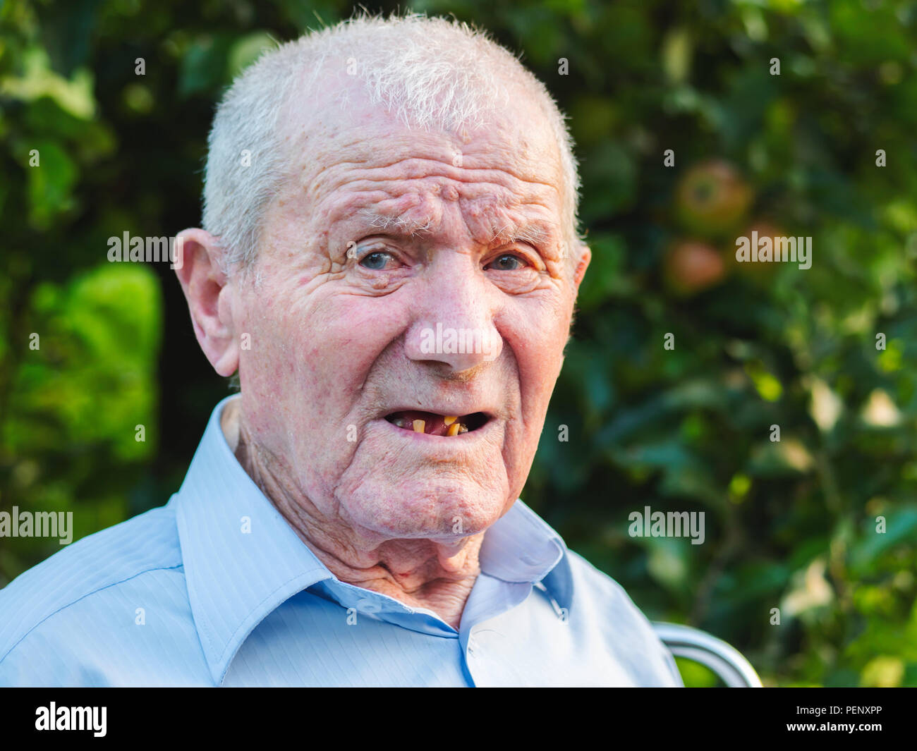 Very old man portrait. Grandfather is looking to camera. Portrait: aged, elderly, senior. Close-up of old man sitting alone outdoors. - Stock Image