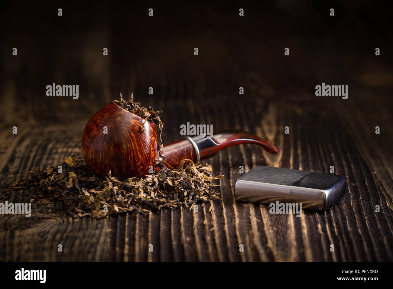 Smoking pipe with tobacco leaves on a rustic wooden table - Stock Image