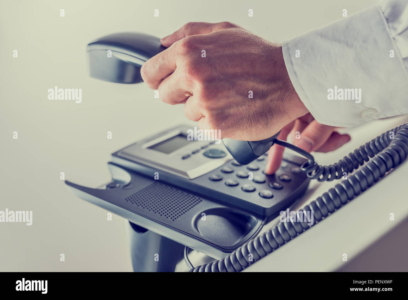 Retro effect faded and toned image of a business man dialing a phone number and picking up handset. - Stock Image