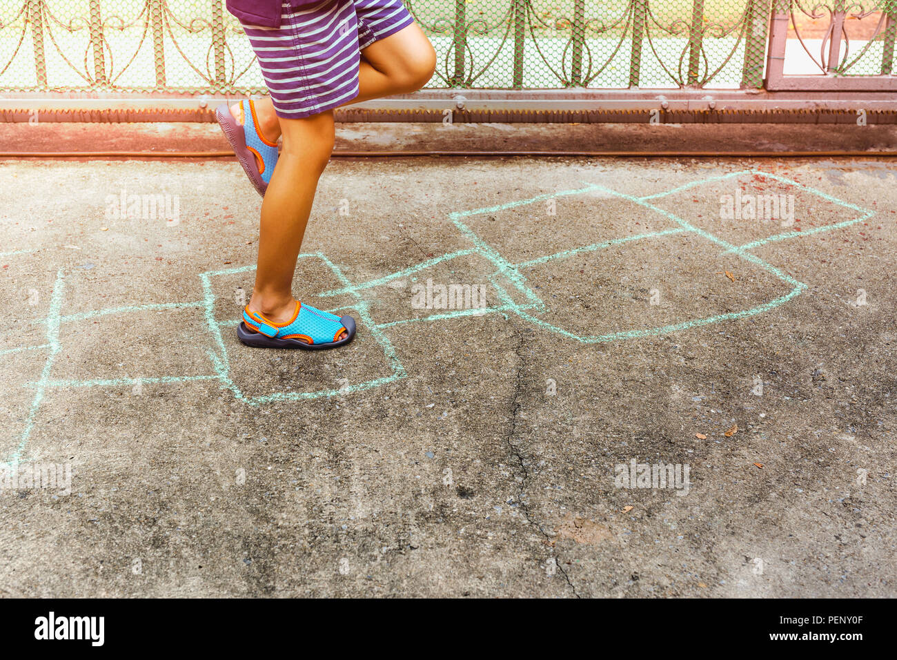 Child playing hopscotch game on concrete floor outdoors in summer. - Stock Image