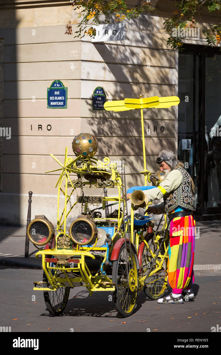 Colorful character repairing his Music-Playing Rickshaw Taxi Contraption, Marais, Paris, France - Stock Image