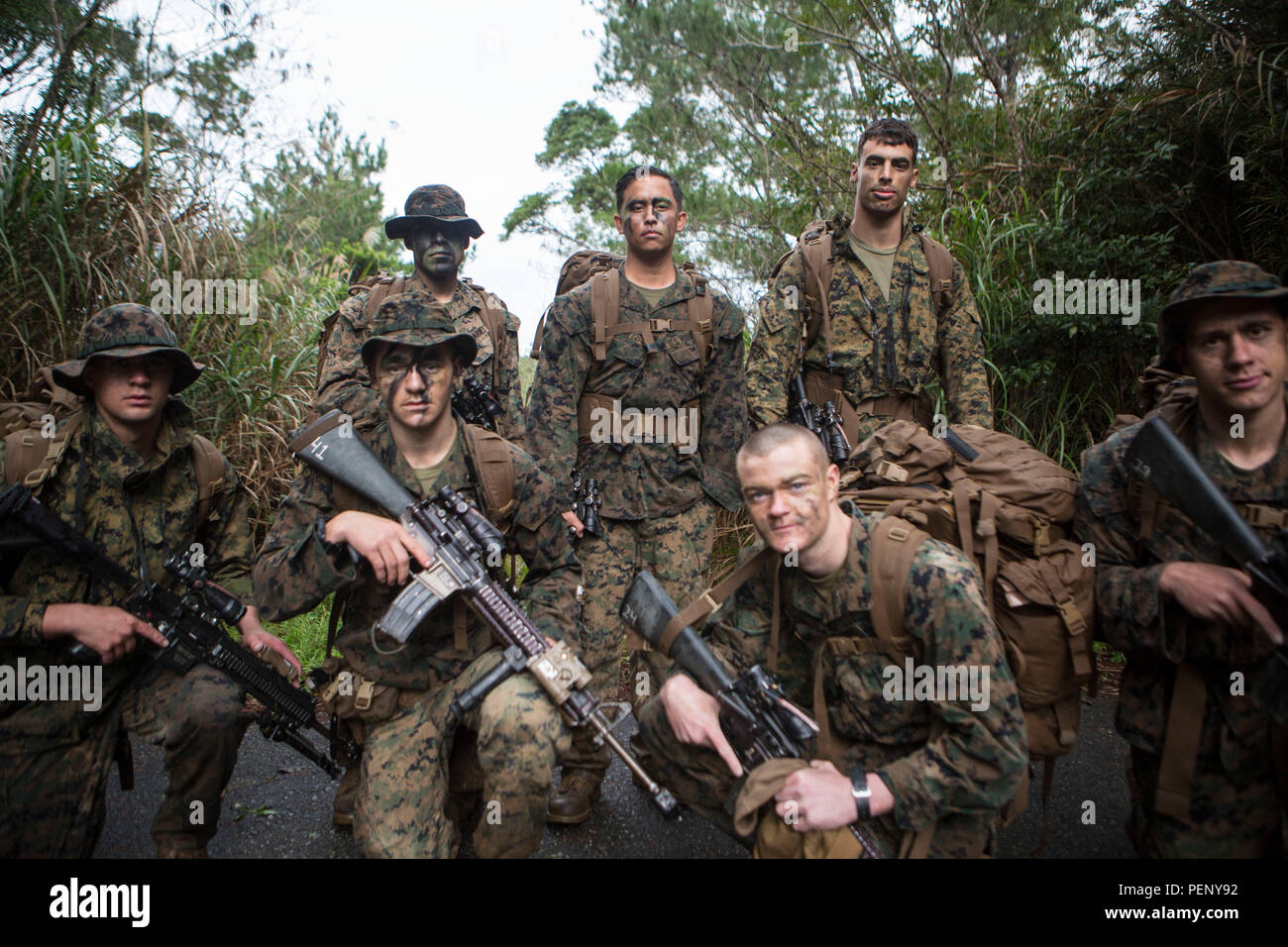 Sgt. Chad Nillo, top row, center, poses for a photo with his squad on Camp Hansen, Okinawa, Japan, Jan. 9, 2016. Sgt. Nillo is currently assigned to Alpha Company, Battalion Landing Team 1st Battalion, 5th Marines, 31st Marine Expeditionary Unit. Nillo has served with Alpha Co., BLT 1/5, 31st MEU, for the past 10 months and has had a great impact on the unit. Nillo is from Newark, California. (U.S. Marine Corps photo by Lance Cpl. Carl King Jr./Released) Stock Photo