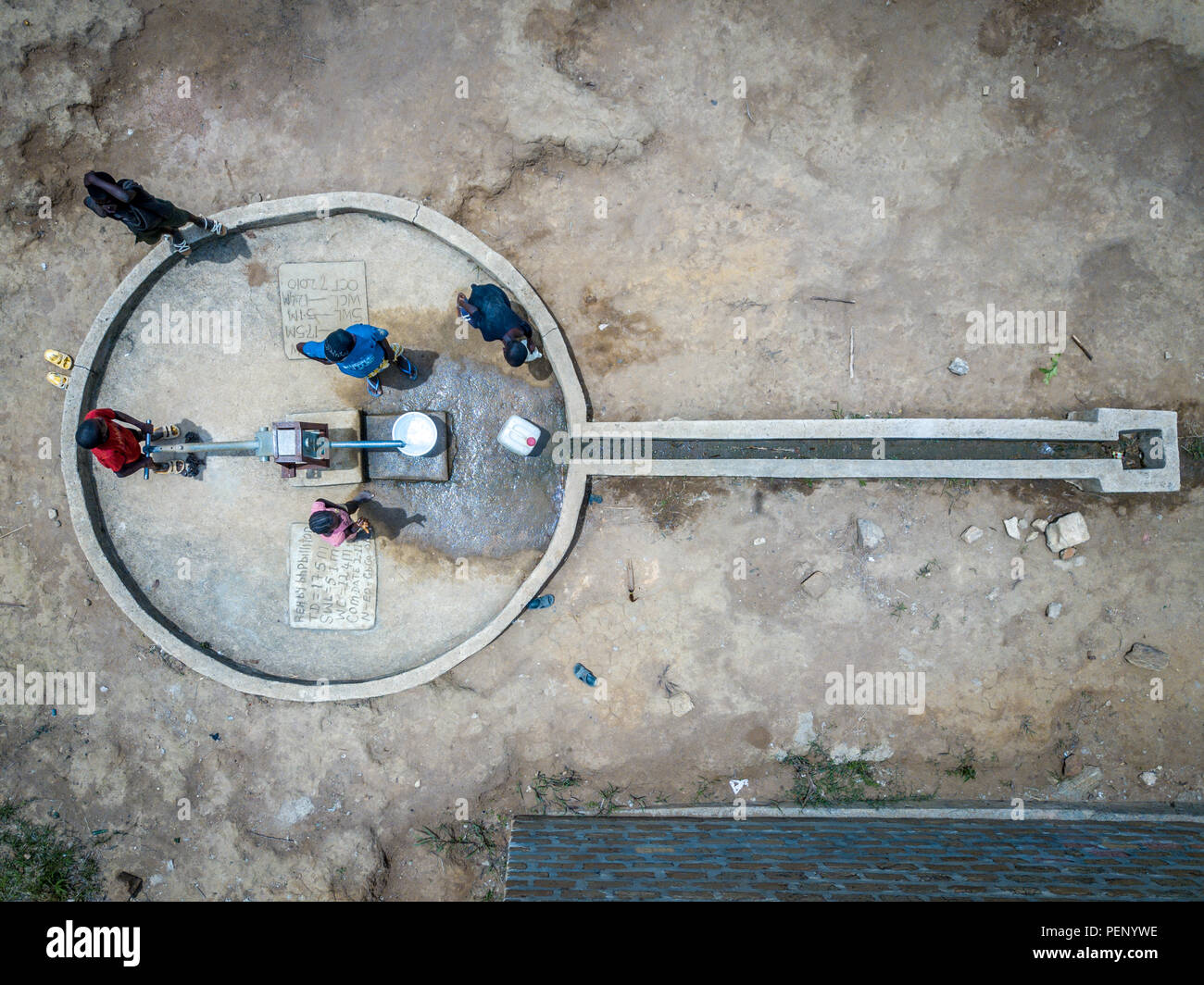 Aerial image of children pumping water at a school in Ganta, Liberia - Stock Image