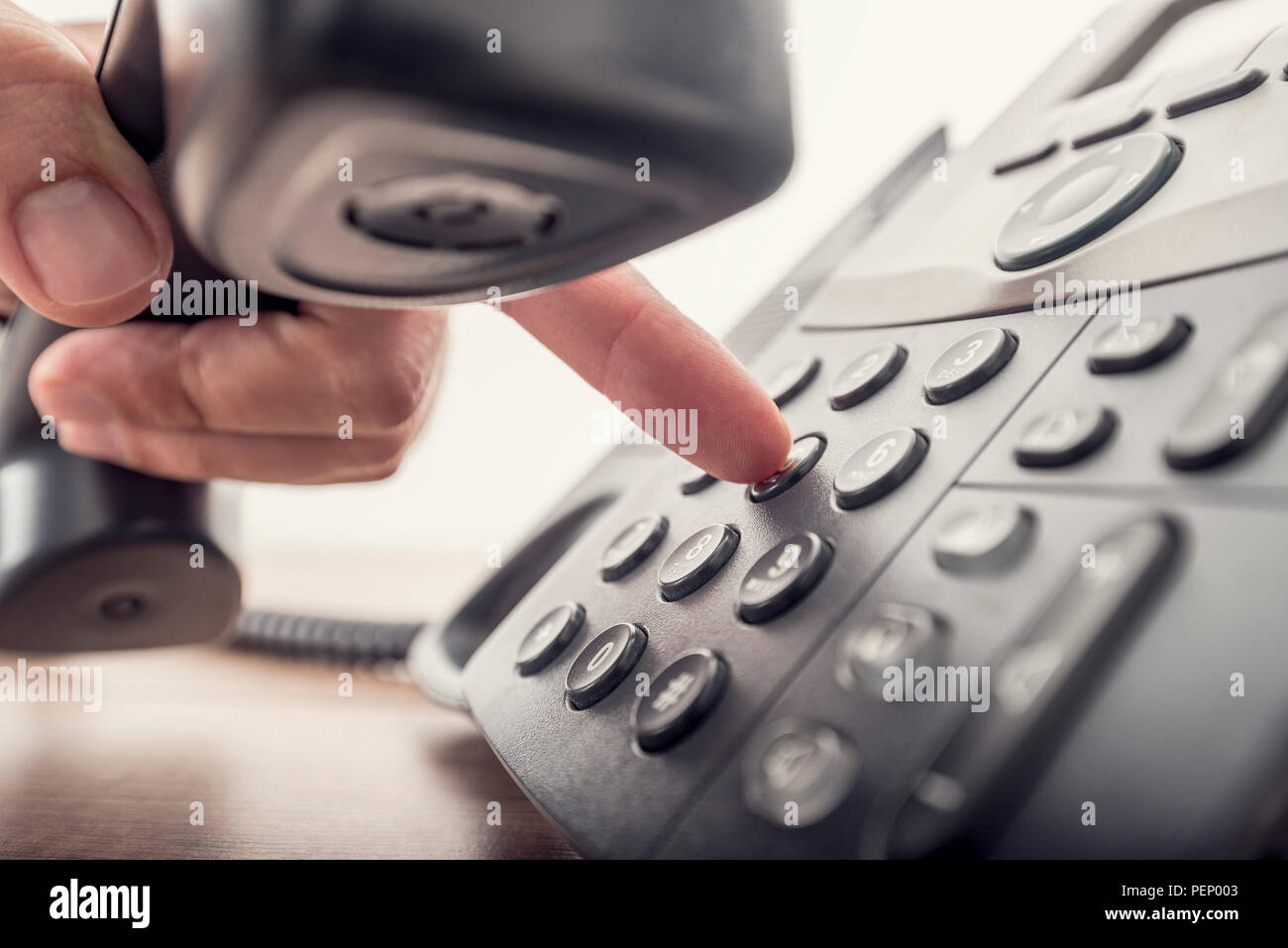 Closeup of male hand holding telephone receiver while dialing a telephone number to make a call using a black landline phone. With retro filter effect - Stock Image