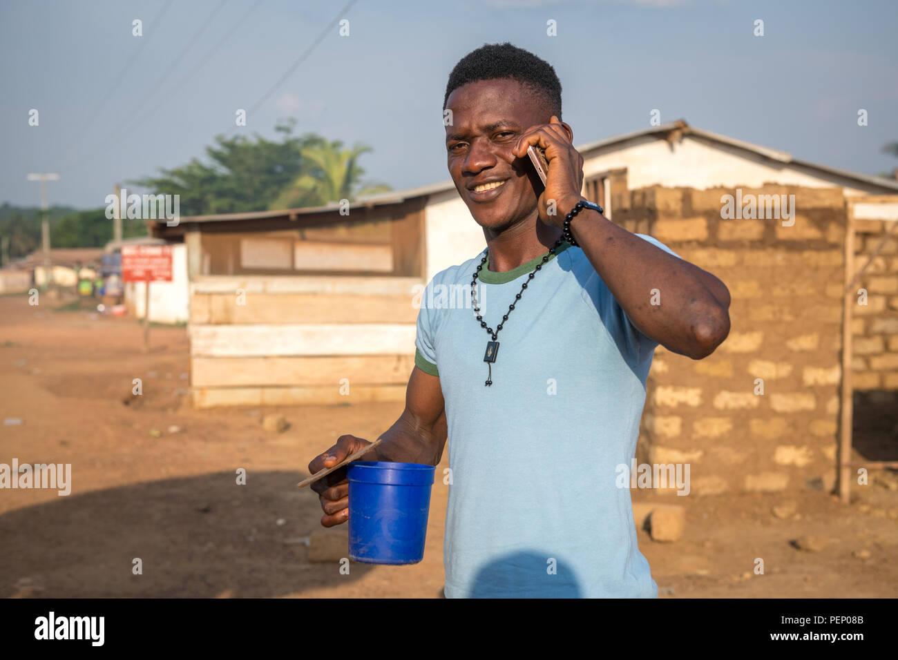 A man on his phone smiles for the camera Ganta, Liberia - Stock Image