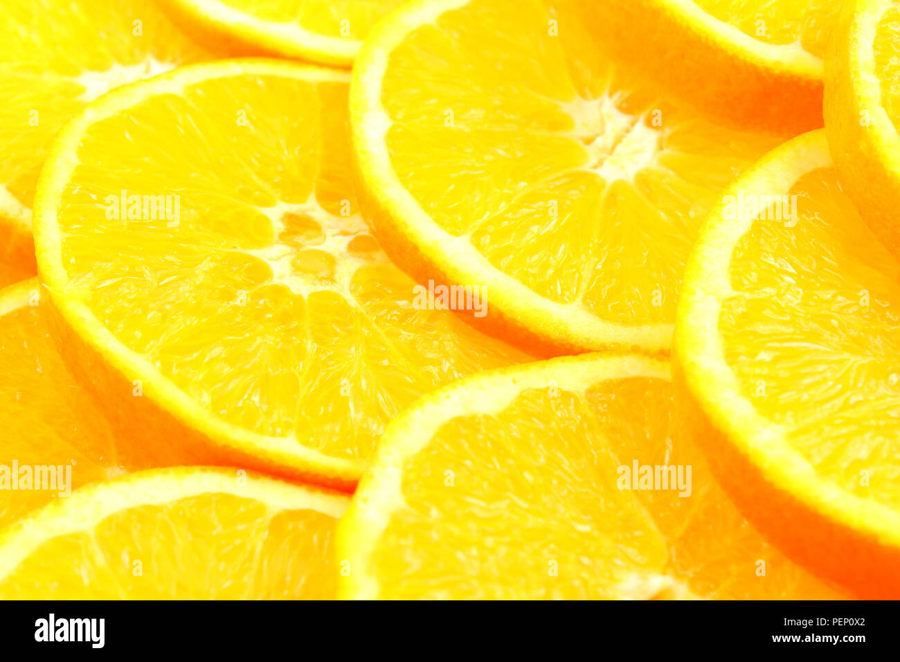 slices of fresh orange fruits as a food background texture - Stock Image
