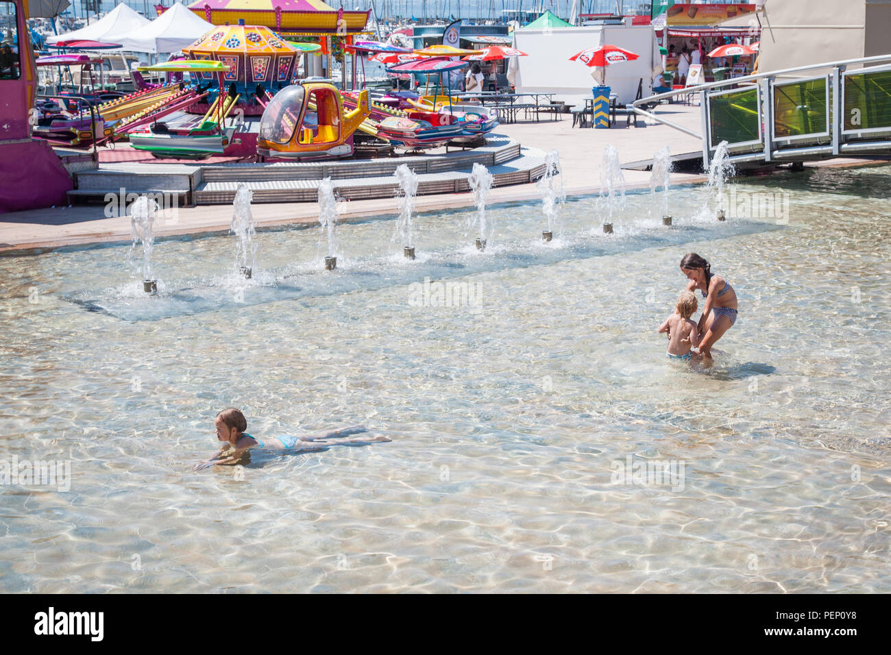 Small kids enjoying playtime in water fountain pool on Place de la Navigation, Ouchy park in Lausanne, Switzerland on hot summer day - Stock Image