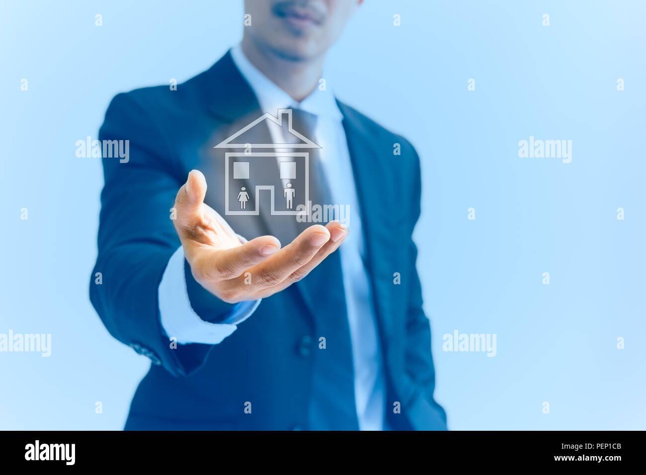 Conceptual businessman hand holding a house with woman and men icon in blue background. - Stock Image
