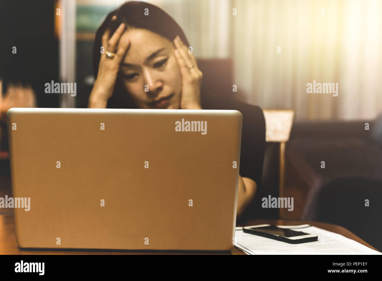 Business woman looking stress working on computer in overtime, Stock Photo