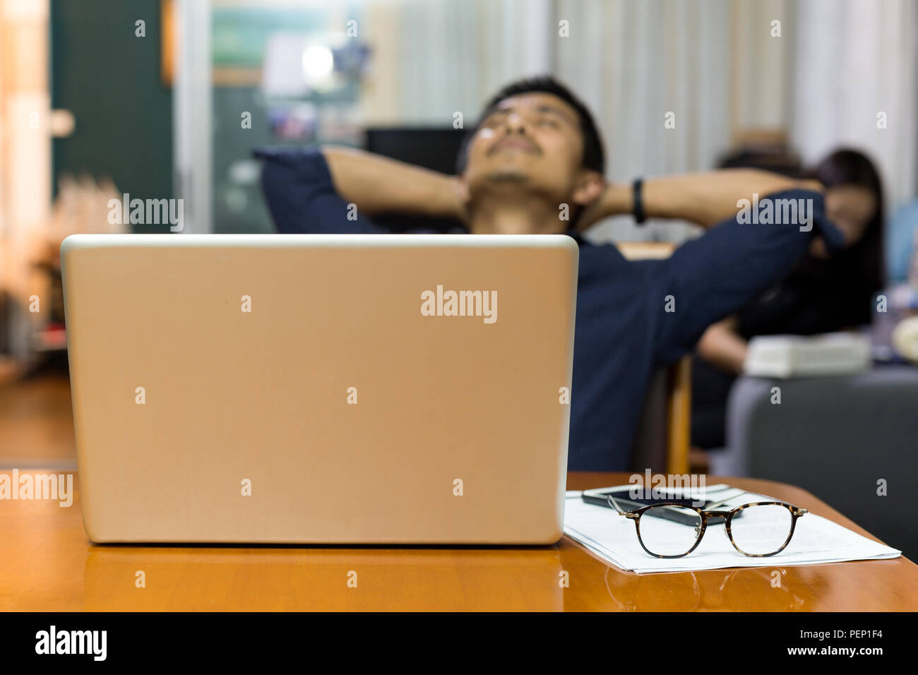 Businessman and laptop taking a moment sitting back with his eyes closed and hands behind his head. - Stock Image