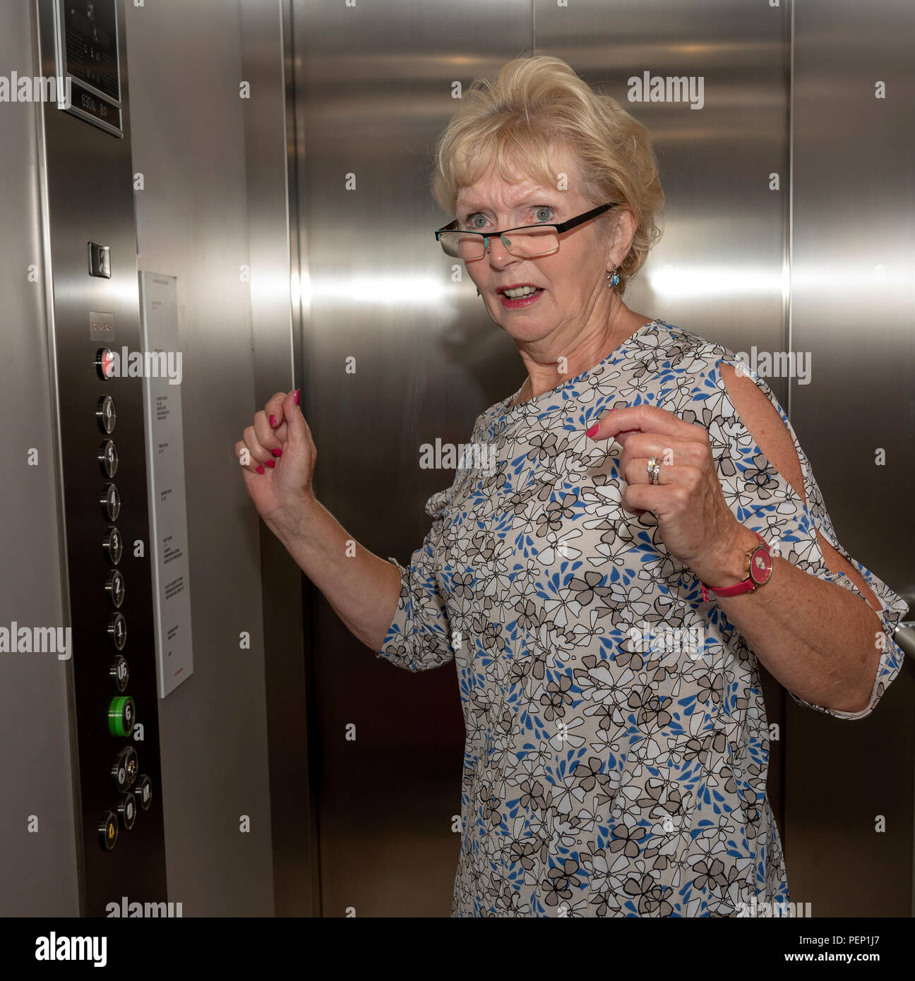 Elderly woman stuck in a lift, raising her arms in fright. - Stock Image