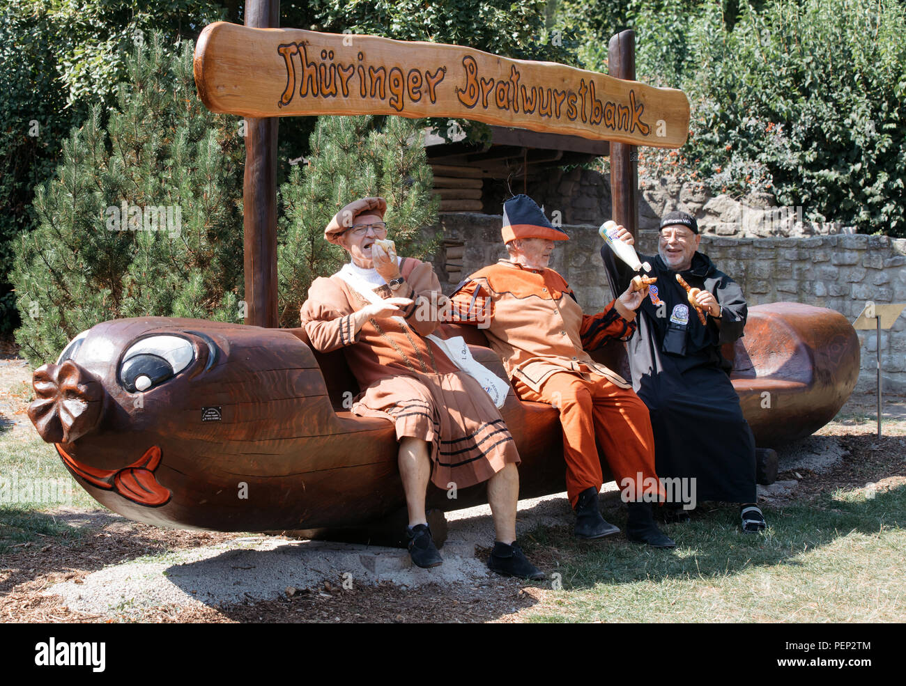 Holzhausen, Germany. 16th Aug, 2018. The traditional figures (l-r) Bernd Knierenschild, Michael Seever and Peter Janke enjoy a sausage on the new Bratwurst bench in the Bratwurstmuseum. Fans of this Thuringian speciality intend to celebrate the 'International Day of the Bratwurst' with new attractions in the Bratwurst Museum every year from today onwards. Credit: Arifoto Ug/Michael Reichel/dpa-Zentralbild/dpa/Alamy Live News Stock Photo