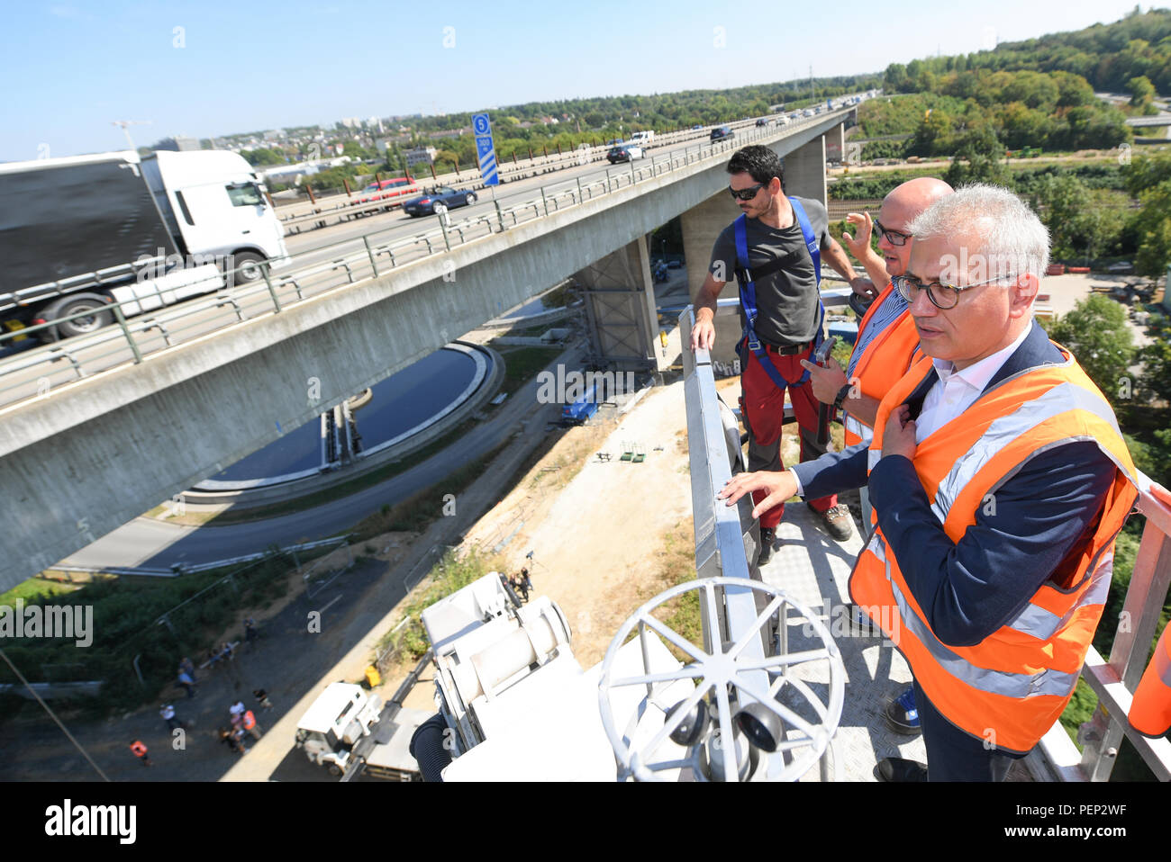 Wiesbaden, Germany. 16th Aug, 2018. Tarek Al-Wazir of the Alliance 90/The Greens, Transport Minister of the State of Hesse, together with bridge inspector Sebastian Krahle (c) from the Hessen Mobil road traffic authority and climber Goran Dadic (l) visit the Wiesbaden Salzbach Valley Bridge (A66 motorway) during a press conference. Hessen Mobil uses the bridge as an example to show how the condition of a bridge is checked. Credit: Arne Dedert/dpa/Alamy Live News - Stock Image