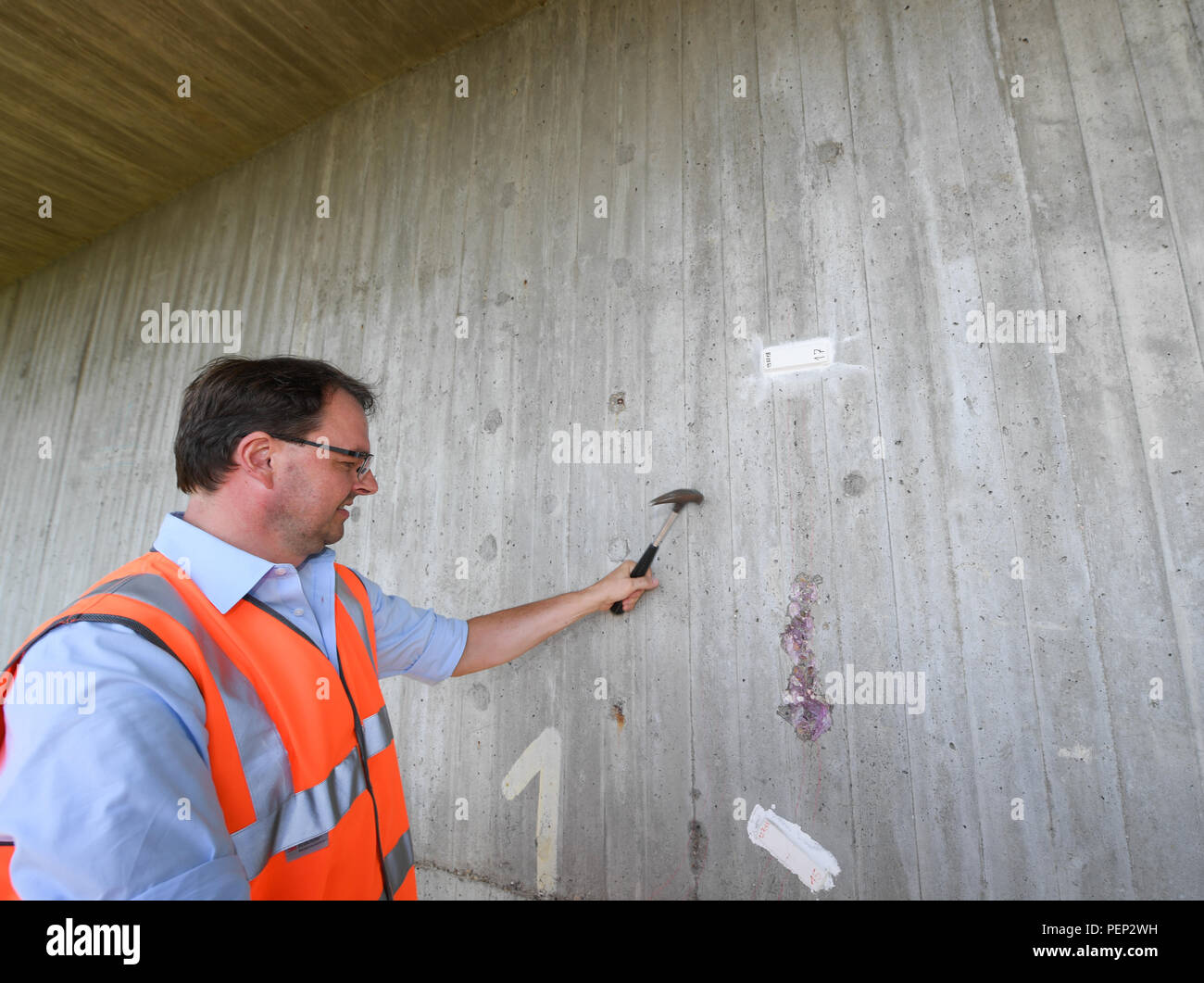 Wiesbaden, Germany. 16th Aug, 2018. Bridge inspector Marco Schmidt of the road traffic authority Hessen Mobil taps at a crack in the wall during a press event at the Salzbach Valley Bridge (Autobahn A66). Hessen Mobil uses the bridge as an example to show how the condition of a bridge is checked. Credit: Arne Dedert/dpa/Alamy Live News - Stock Image