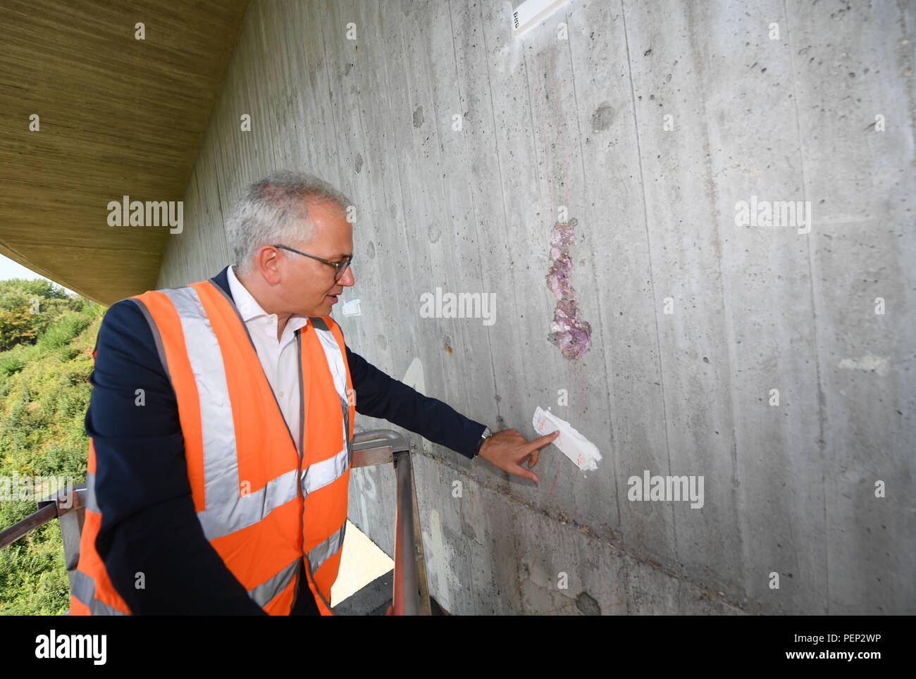 Wiesbaden, Germany. 16th Aug, 2018. Tarek Al-Wazir (Alliance 90/The Greens), Minister of Transport of the State of Hesse, inspects a spot with a crack during a press event at the Salzbach Valley Bridge (Autobahn A66) in Wiesbaden. Hessen Mobil uses the bridge as an example to show how the condition of a bridge is checked. Credit: Arne Dedert/dpa/Alamy Live News - Stock Image