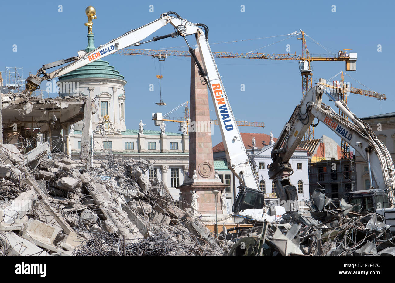 16 August 2018, Germany, Potsdam: Excavators demolish the last remains of the building of the old University of Applied Sciences against the backdrop of the Old Town Hall. Construction of new buildings on the site is scheduled to begin in 2019 and the site is scheduled for completion in 2021. Photo: Ralf Hirschberger/dpa - Stock Image