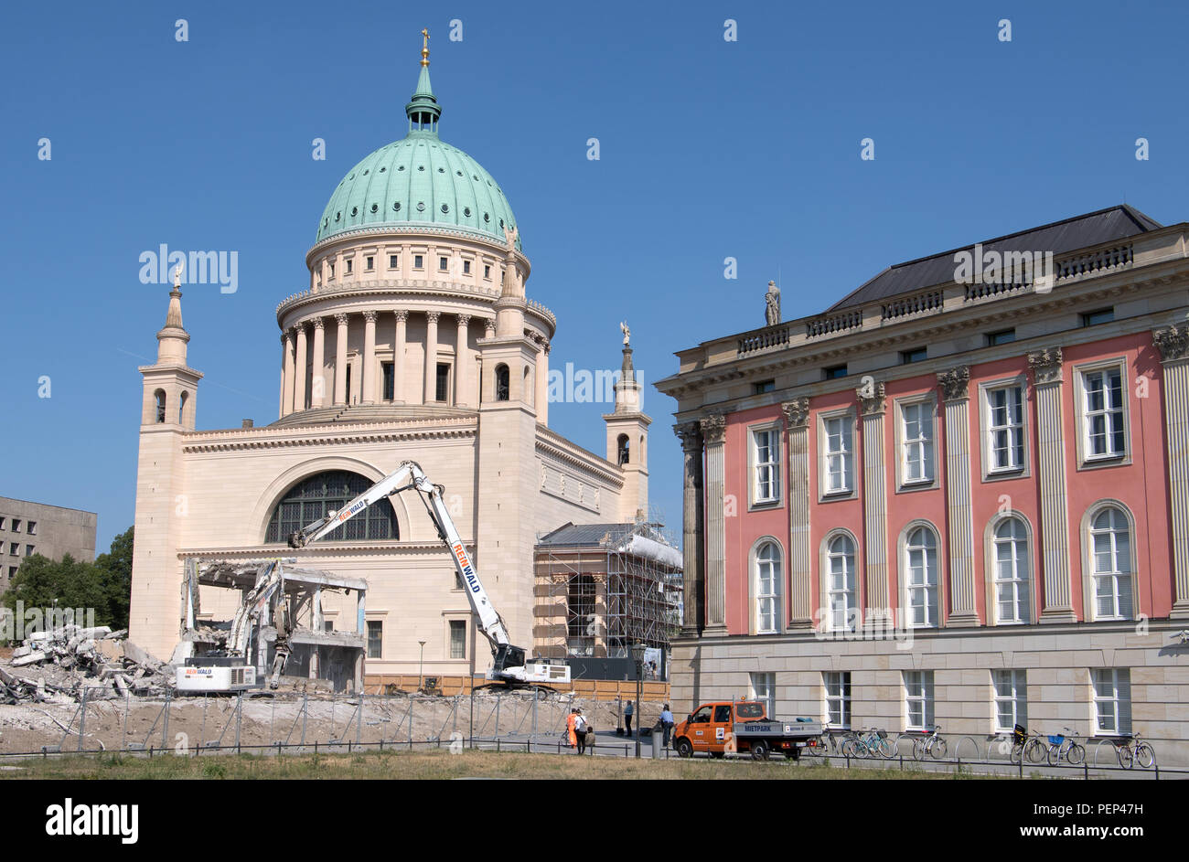 16 August 2018, Germany, Potsdam: Excavators demolish the last remains of the building of the old University of Applied Sciences against the backdrop of the Nikolaikirche. Construction of new buildings on the site is scheduled to begin in 2019 and the site is scheduled for completion in 2021. Photo: Ralf Hirschberger/dpa - Stock Image