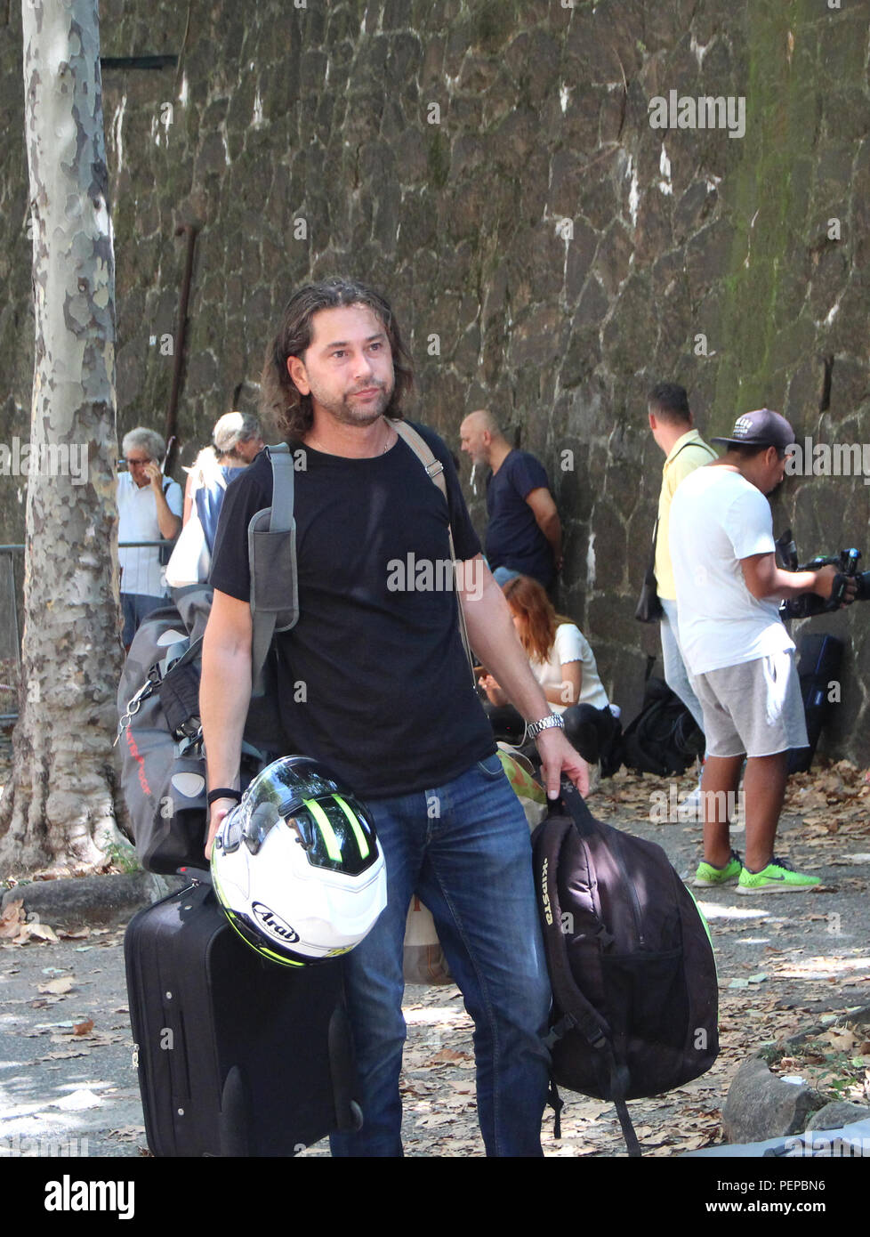 Genoa, Italy. 16th Aug, 2018. Luca walks with his suitcase and bags and a motorcycle helmet in his hand to his two-wheeler. Luca is one of the tenants of the eleven houses who were evacuated after a bridge collapsed. (to dpa ''Zero hour for Genoa' - catastrophe plunges city into crisis' of 17.08.2018) Credit: Fabian Nitschmann/dpa/Alamy Live News - Stock Image