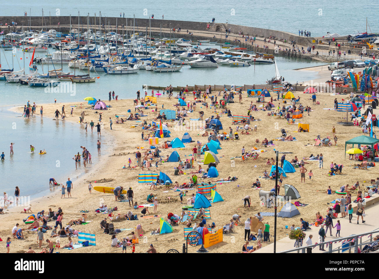 Lyme Regis, Dorset, UK. 17th Aug, 2018. UK Weather: Holidaymakers flock to the beach to enjoy a morning of hot sunny spells in Lyme Regis. The picturesque beach at the seaside resort of Lyme Regis was busy again this morning as thick cloud is broken by long spells of hot sunshine. Credit: Celia McMahon/Alamy Live News - Stock Image