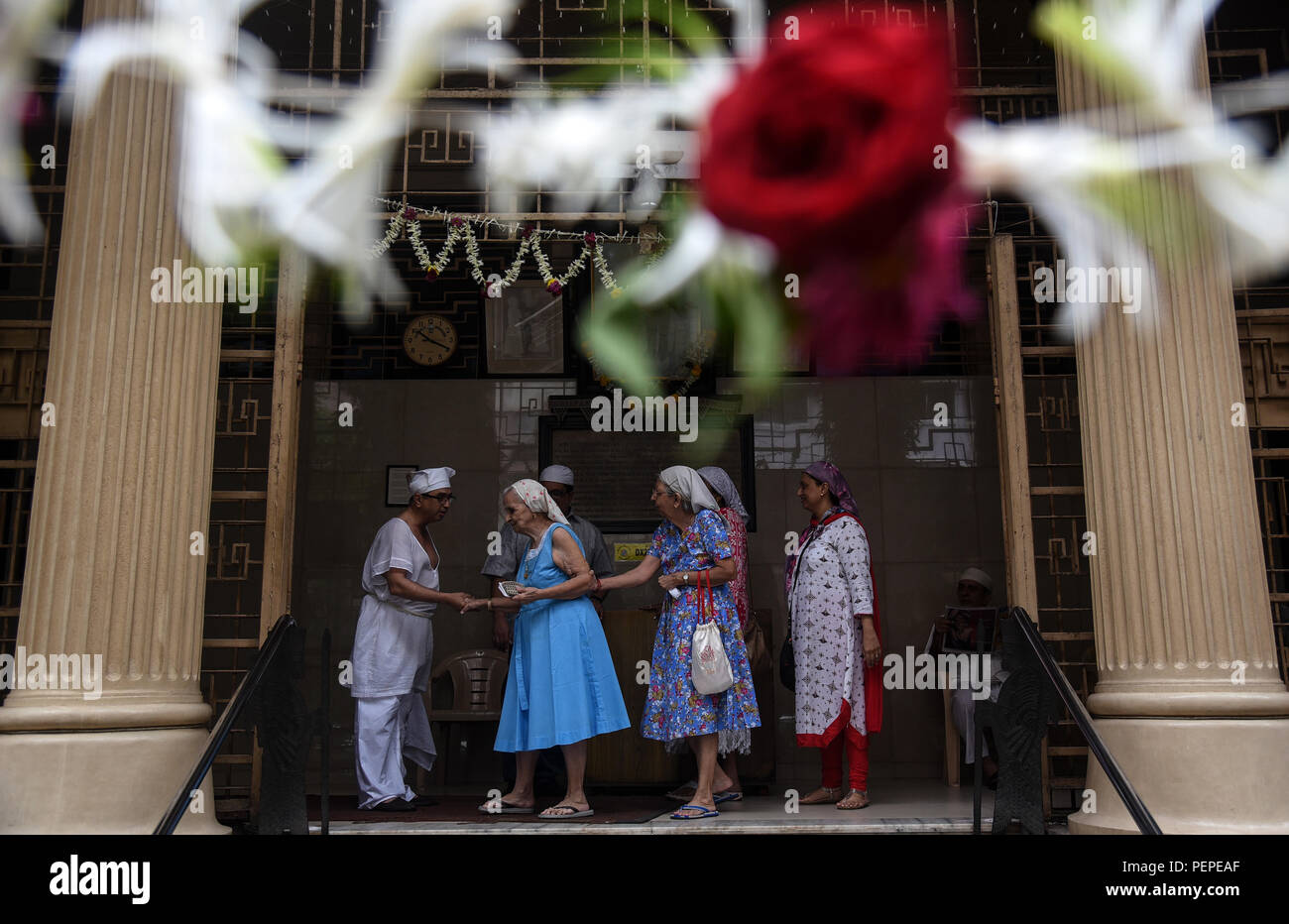 Mumbai, India. 17th Aug, 2018. Indian Zoroastrians or Parsi people greet each other on the occasion of Nowruz, the Parsi New Year day, in Mumbai, India, Aug. 17, 2018. Parsis are the followers of the ancient Persian religion known as Zoroastrianism, living mostly in India, Iran and Pakistan. Credit: Stringer/Xinhua/Alamy Live News - Stock Image